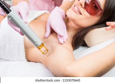 Laser cosmetology Armpit hair removal. Beautiful smiling woman client in red glasses having procedure.