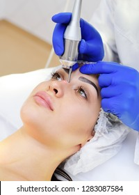 Laser cosmetology. The doctor removes pigmentation-moles or warts patient neodymium laser.
