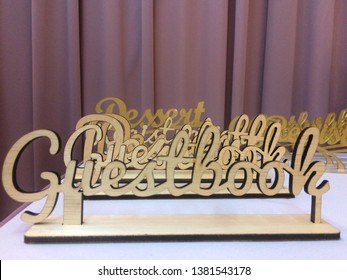Laser cut wood wording 'GUESTBOOK' on table