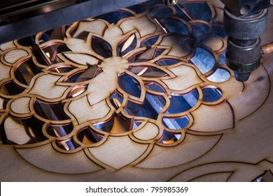 laser cuts out a tree in the form of a mandala