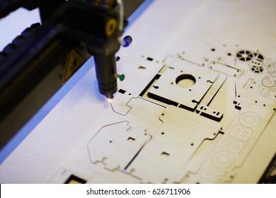 Laser cutter engraving details from veneer wood