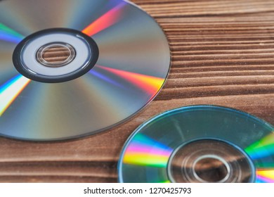 Laser discs are on a wooden table.