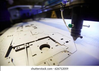 Laser engraving machine cutting details from plywood sheet