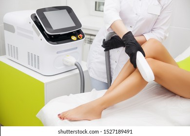 Laser epilation and cosmetology in beauty salon. Hair removal procedure. Laser epilation, cosmetology, spa, and hair removal concept. Beautiful brunette woman getting hair removing on legs