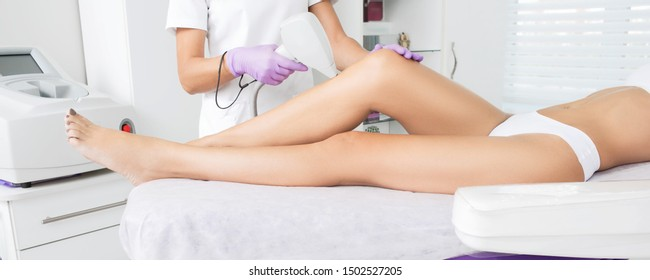 laser epilation on beautiful female legs at beauty clinic