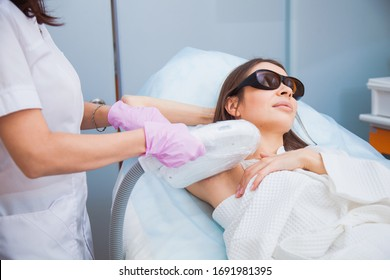 Laser hair removal, photoepilation, body and skin care concept. Young woman remove hair on armpits at cosmetology clinic. Closeup shot, hygiene procedure concept