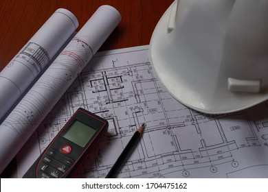 Laser meter, white hardhat and drawings at engineer workplace