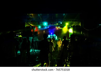 Laser show. Luminous performance at nightclub party. Creative Light show, silhouettes of crowd on dance floor. light picture in smoke of smoke machine. Stylized  film, grain, distortion, motion blur
