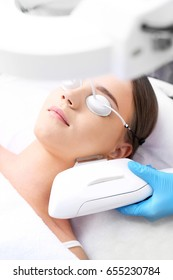 Laser therapy in the office of aesthetic medicine.Cosmetic clinic, woman during laser facial surgery.