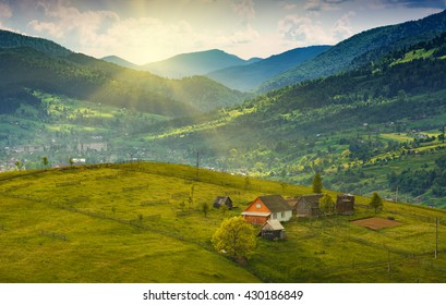 Laseshina village on a mountain hill, covered with fresh green grass in a sunset light. Carpathian landscape. Spring time