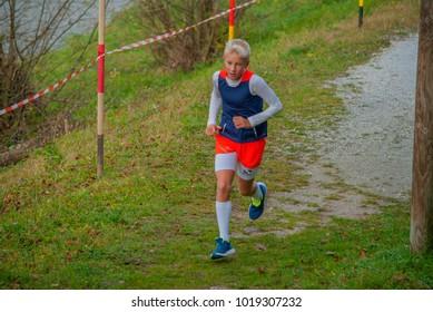 LASKO, SLOVENIA, 11.11.2017, Charity run: Boy runner beside river.