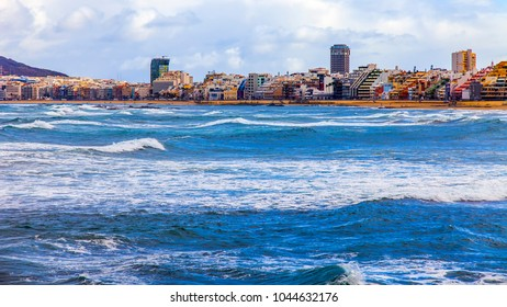 Las-Palmas de Gran Canaria, Spain, on January 6, 2018. The winter sun lights the Playa de Las Canteras beach on the bank of the Atlantic Ocean. Nice waterfront in a distance