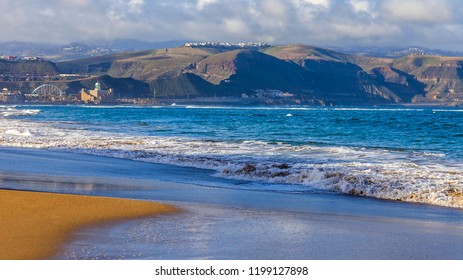 Las-Palmas de Gran Canaria, Spain, on January 6, 2018. The winter sun lights the Playa de Las Canteras beach on the bank of the Atlantic Ocean and the beautiful embankment in the distance.