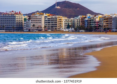 Las-Palmas de Gran Canaria, Spain, on January 8, 2018. The Playa de Las Canteras beach on the bank of the Atlantic Ocean and picturesque waves in the winter. beautiful embankment in the distance