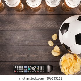 lasses of beer with snack and soccer ball on wooden. Copy space. Flat