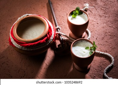 lassie or lassi is an Authentic cold drink from Punjab province, India. Made up of curd, milk and sugar in earthen pot or matka and served in terracotta glasses. moody background and Selective focus