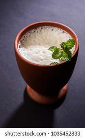 Lassie or lassi in terracotta glass - Lassi is an Authentic Indian cold drink made up of curd and milk and sugar, selective focus