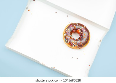 Last chocolate donut in empty box on pastel blue background