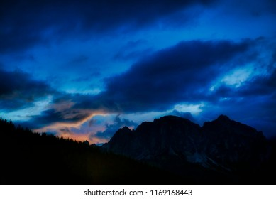 last color of sunset during the blue hour over the mountains of Alta Badia with cloudy sky, Dolomites - Italy