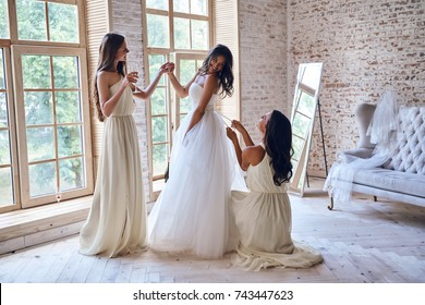 Last details. Full length of two attractive young women adjusting a wedding dress on a beautiful bride