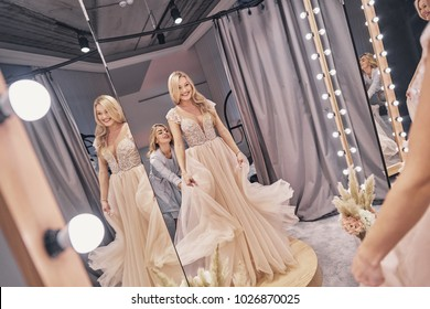 Last details.  Reflection of attractive young woman adjusting a wedding dress on a bride while standing in the fitting room