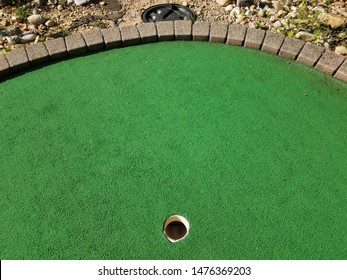 last hole on a miniature golf course with pipe to ball collection bucket