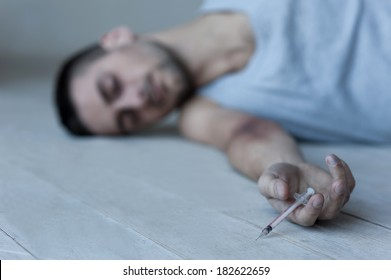 The last injection. Young man lying on the floor and keeping eyes closed while holding syringe in his hand