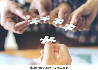 Last jigsaw - close up hand of group business partnership people puting together a jigsaw puzzle  , business teamwork Strategy solution concept