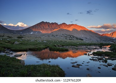 last light of day on Split Mountain a fourteen thousand foot tall mountain in California from the west reflected in water