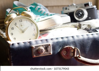 Last minute to travel concept with clock and open suitcase
