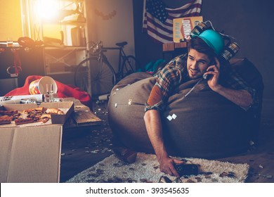Last night was awesome! Handsome young man talking on mobile phone and holding joystick while lying on bean bag in messy room after party