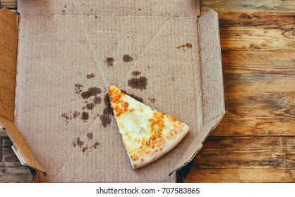 last piece of fresh pizza four cheeses in cardboard box on wooden table, food delivery