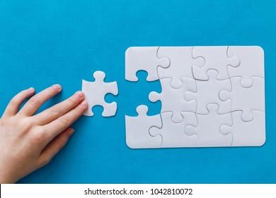 Last piece jigsaw in hand. Concept success of business. Blue background