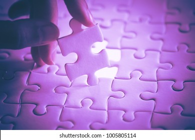 last piece of white plain jigsaw holding by hand, step of success concept, ultraviolet tone