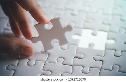 last piece of white plain jigsaw holding by hand, step of success concept