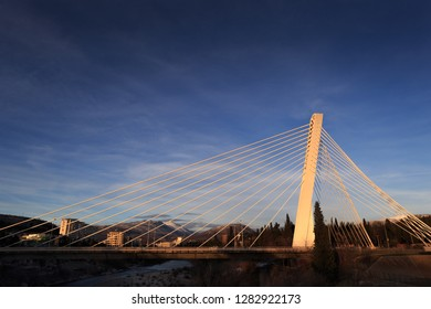 Last rays of setting sun hit the Millenium bridge, symbol of Podgorica, Montenegro. Golden light and deep blue sky with some clouds.