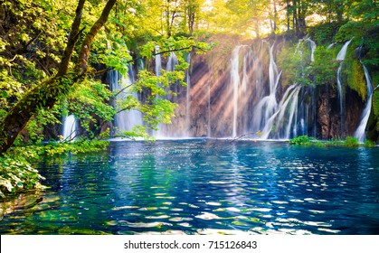 Last sunlight lights up the pure water waterfall on Plitvice National Park. Colorful spring scene of green forest with blue lake. Great countryside view of Croatia. Beauty of nature concept background