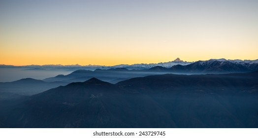Last sunlight on the alpine arc with the majestic peak of M. Viso (3841 m) arising from the misty valley below. Panoramic frame, high contrast. Aerial view on the Susa Valley, Torino Province, Italy.