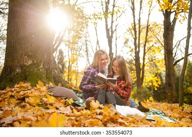 Last warm days. Young teenage daughter reading a book together with her beautiful mother sitting on the plaid in the forest