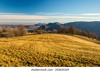 Last warm sunlight of the day on alpine wide pasture over the valley. Wide angle view from the glowing grassy slope. Susa Valley, Italian Alps.
