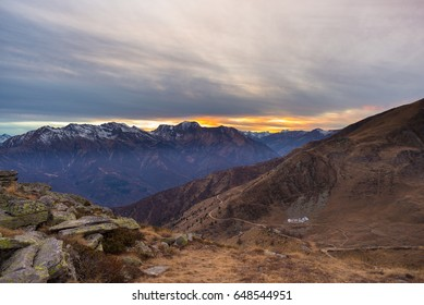 Last warm sunlight on alpine valley with glowing mountain peaks and scenic clouds. Italian French Alps, summer travel destination.