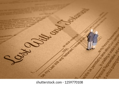 Last will and testament / legacy, inheritance or death tax concept : Miniature elder / old couple stands on a legal document form, depicts preparing to transfer properties to their heirs after death