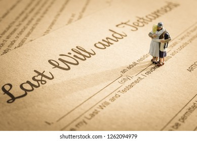 Last will and testament / legacy, inheritance or death tax concept : Miniature elder / old couple family on a legal document form, depicts preparing to transfer properties to their heirs after death