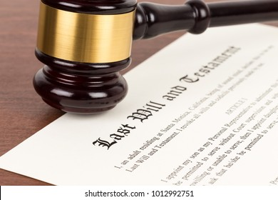 Last will and testament on yellowish paper with wooden judge gavel; document is mock-up
