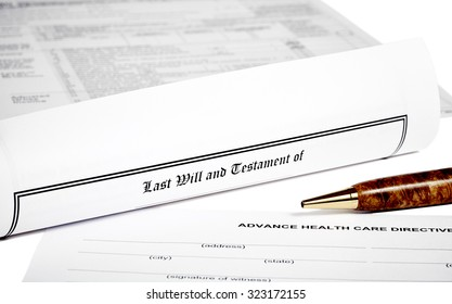 Last Will and Testament rolled up with advance health care directive isolated on white with a pen