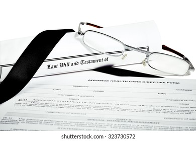 Last Will and Testament rolled up with reading glasses isoated on white with a black ribbon and Advance Health Care Directive