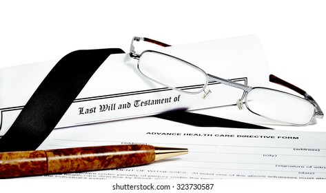 Last Will and Testament rolled up with reading glasses and pen isoated on white with a black ribbon and health care directive