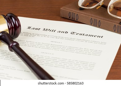 Last will and testament with wooden judge gavel; document is mock-up not real