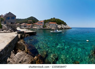LASTOVO / CROATIA - AUG 15, 2018: Yachts and fishing boats moored in front of the traditional Dalmatian restaurants (taverns or konobas).