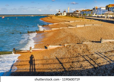 late afternoon autumn sunshine turns the pebbles on the beach and wooden groyne water breakers in Herne Bay, Kent, Uk a golden colour. A shadow of a photogpraher can be seen leaning on a fence